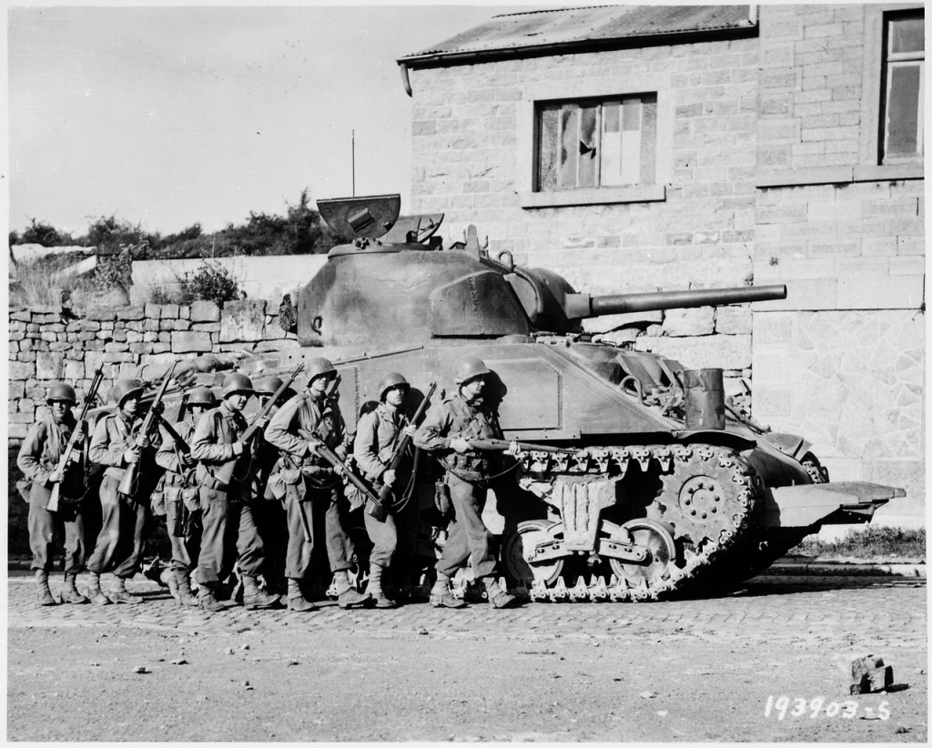 Yanks_of_60th_Infantry_Regiment_advance_into_a_Belgian_town_under_the_protection_of_a_heavy_tank._-_NARA_-_531213.tif