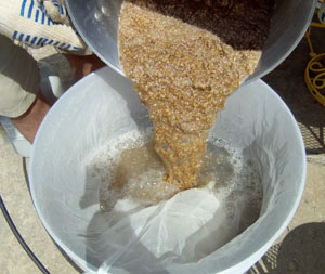 After the mash rest, the mash is poured into the sparge water in the bag-lined kettle.