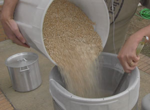 Pouring in 20 pounds of grain to get the process started.